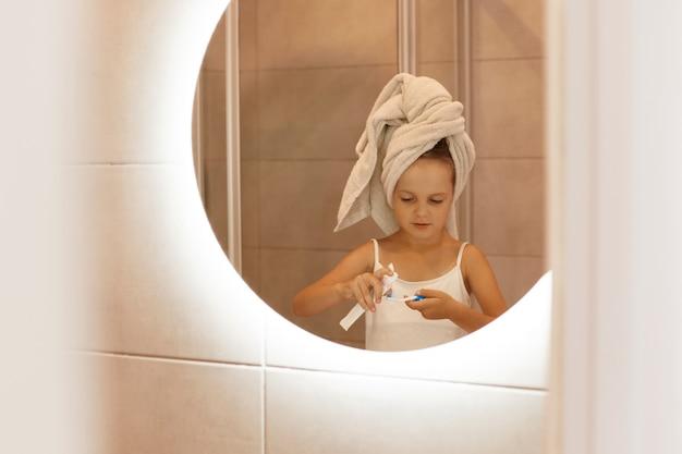 Retrato de uma menina escovando os dentes no banho em frente ao espelho, sendo enrolada em uma toalha branca, espremendo a pasta de dente de um tubo, rotina matinal.