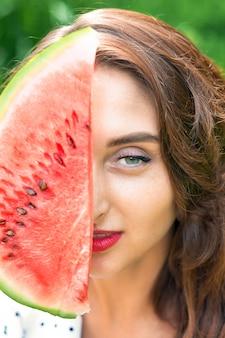 Retrato de uma menina está segurando a fatia de melancia, cobrindo parte do rosto.