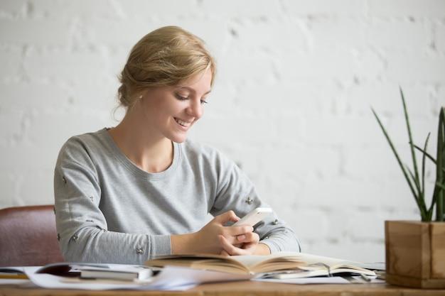 Retrato de uma menina estudante na mesa com o telefone