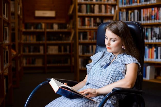 Retrato de uma menina estudante sentado numa poltrona confortável e lendo um livro