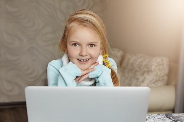 Retrato de uma menina europeia loira com um rabo de cavalo bagunçado com uma expressão alegre e feliz
