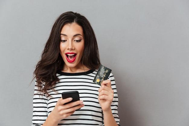 Retrato de uma menina excitada olhando para o telefone móvel