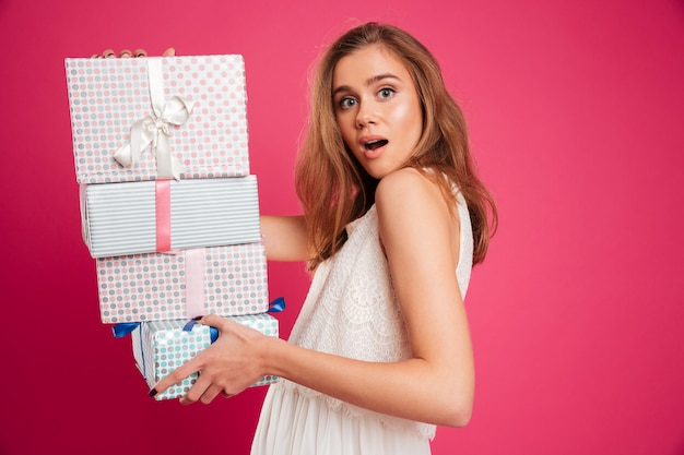 Retrato de uma menina excitada segurando a pilha de caixas de presente
