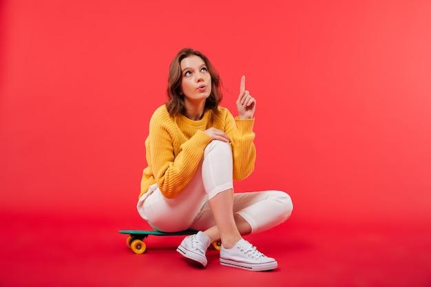 Retrato de uma menina excitada sentado em um skate