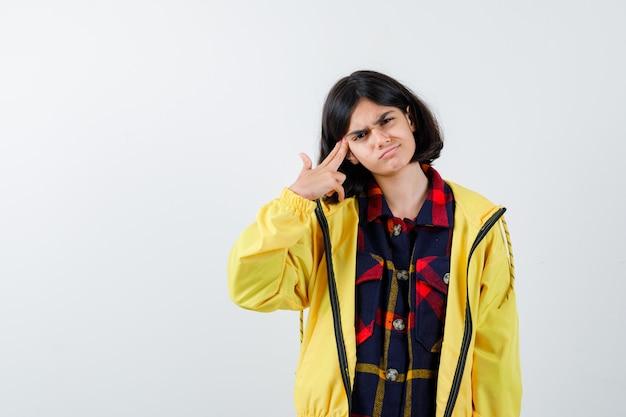 Retrato de uma menina fazendo gesto de suicídio em uma camisa quadrada, jaqueta e olhando estressado de frente
