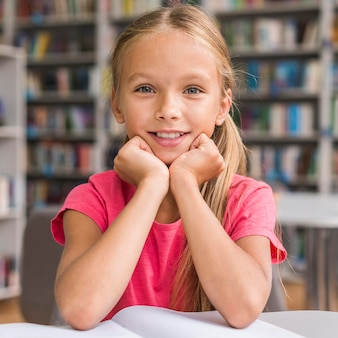Retrato de uma menina fazendo lição de casa na biblioteca