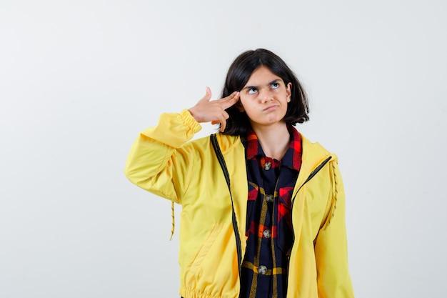 Retrato de uma menina fazendo um gesto de suicídio com uma camisa quadrada, jaqueta e uma vista frontal sem esperança