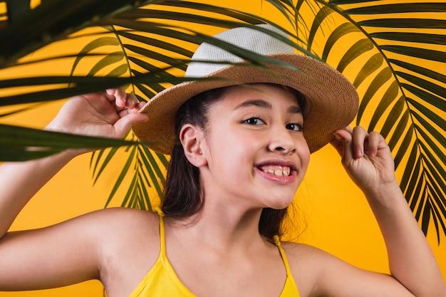 Retrato de uma menina feliz com chapéu e folhas de palmeira em fundo amarelo.