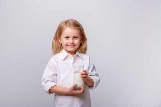 Retrato de uma menina feliz com óculos e um copo de leite.