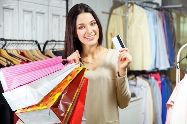 Retrato de uma menina feliz com sacos de compras e cartão de crédito em uma loja de roupas.
