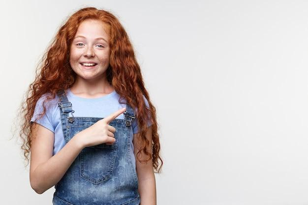 Retrato de uma menina feliz com sardas fofas com cabelo ruivo, quer chamar a atenção para o espaço da cópia no lado direito e aponta com os dedos, fica sobre uma parede branca e amplamente sorridente.