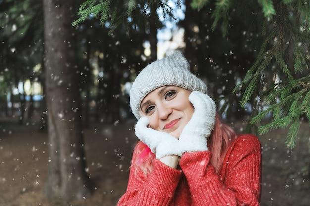 Retrato de uma menina feliz com um chapéu de malha, luvas e uma camisola vermelha entre uma floresta de abetos de inverno e neve caindo.