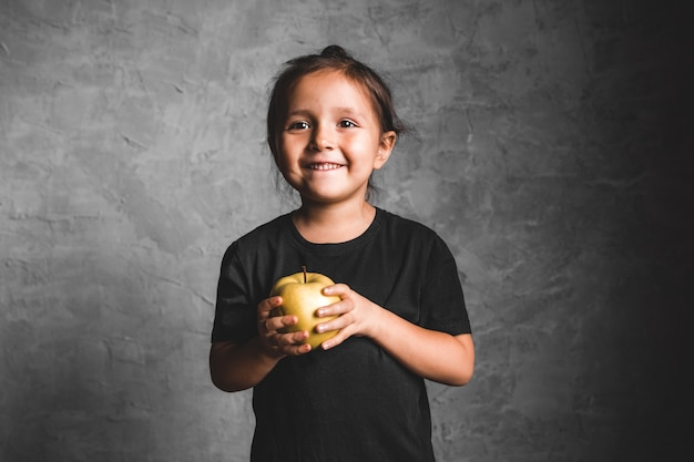 Retrato de uma menina feliz comendo uma maçã verde em cinza
