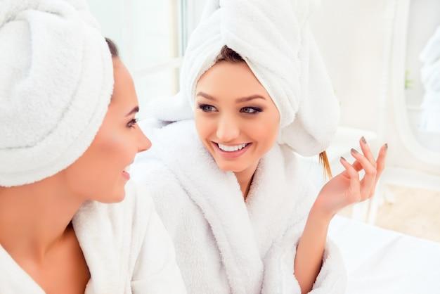 Retrato de uma menina feliz e alegre em um manto conversando com a amiga