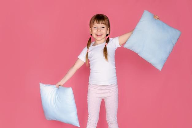 Retrato de uma menina feliz e fofa de 5 a 6 anos abraçando seu travesseiro macio, aproveite o fim de semana, sinta-se confortável, vá para a cama, coloque uma roupa de dormir branca isolada sobre um fundo rosa