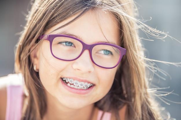 Retrato de uma menina feliz e sorridente com aparelho dentário e óculos.