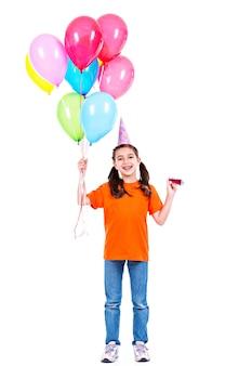 Retrato de uma menina feliz e sorridente em camiseta laranja segurando balões coloridos - isolados em um branco.