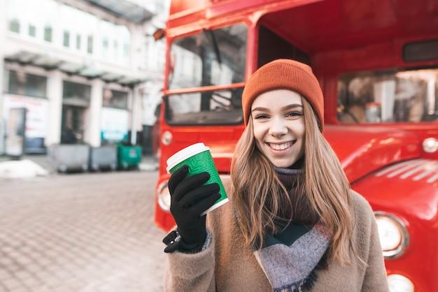 Retrato de uma menina feliz em roupas quentes em pé na rua com uma xícara de café