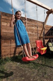 Retrato de uma menina feliz em um vestido azul, brincando ao ar livre, ela balançando