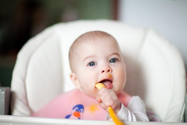 Retrato de uma menina feliz em uma cadeira alta comendo um bebê