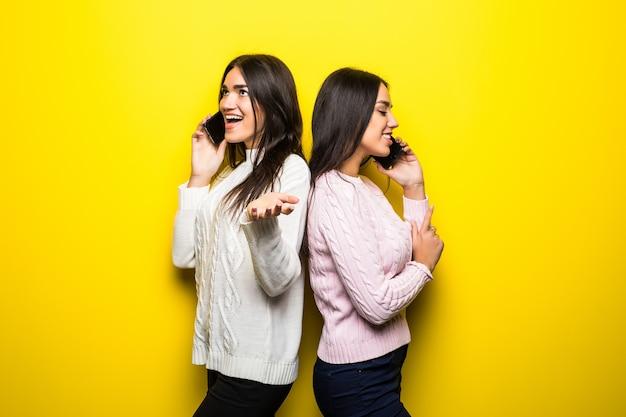 Retrato de uma menina feliz falando em telefones celulares isolados sobre a parede amarela