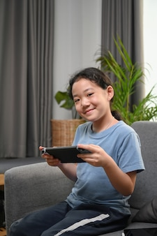 Retrato de uma menina feliz jogando videogame enquanto está sentada no sofá em casa