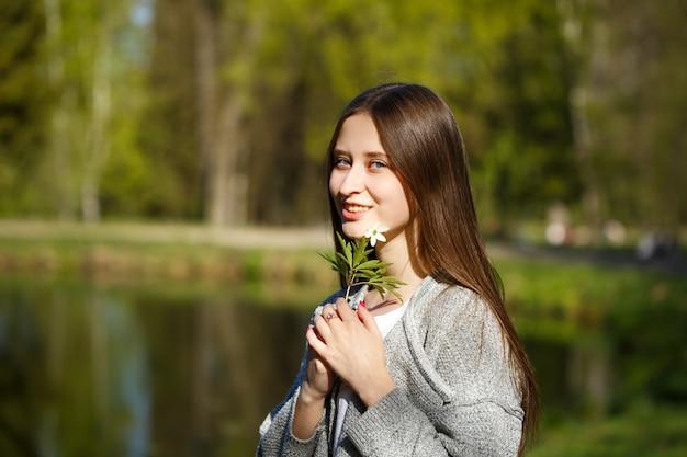 Retrato de uma menina feliz no fundo de um parque com um lago, segurando uma flor da floresta selvagem. dia ensolarado de primavera
