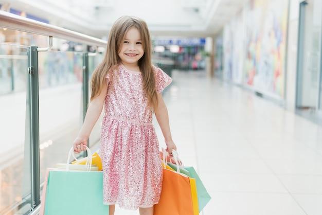 Retrato de uma menina feliz no shopping. uma garota rindo sorridente em um vestido rosa com sacos multicoloridos nas mãos dela está envolvida em compras. modelo para o seu anúncio