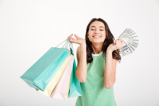 Retrato de uma menina feliz num vestido segurando sacolas de compras
