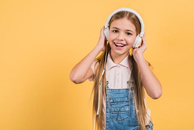 Retrato de uma menina feliz ouvindo música no fone de ouvido contra o pano de fundo amarelo