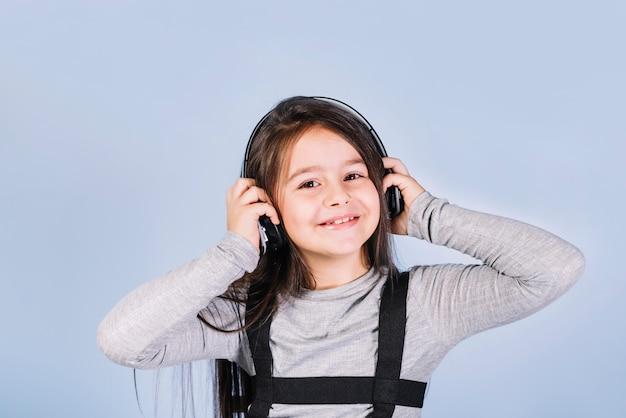 Retrato de uma menina feliz ouvindo música no fone de ouvido contra o pano de fundo azul