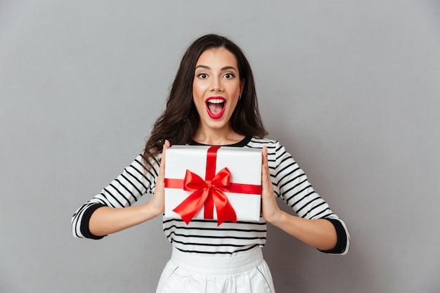 Retrato de uma menina feliz, segurando a caixa de presente