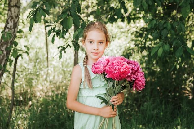 Retrato de uma menina feliz, segurando nas mãos um buquê de flores de peônia rosa em plena floração