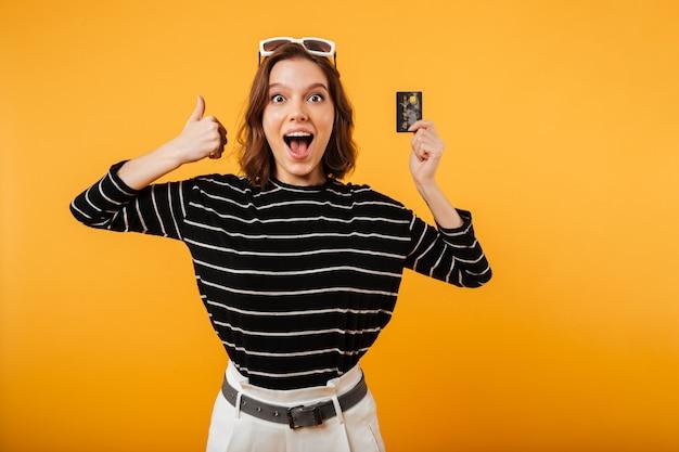 Retrato de uma menina feliz, segurando o cartão de crédito
