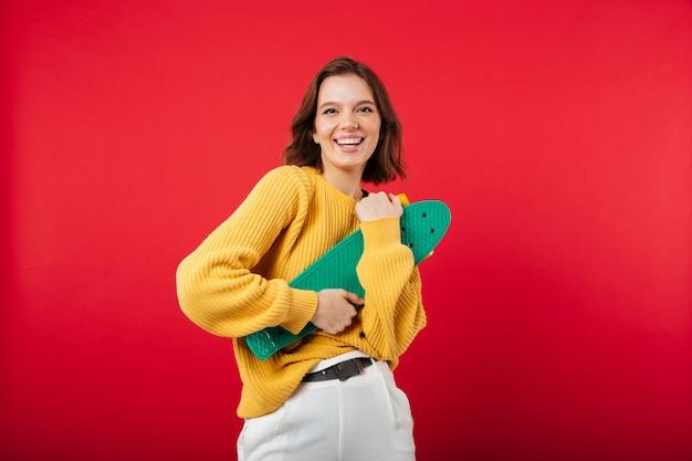 Retrato de uma menina feliz, segurando o skate