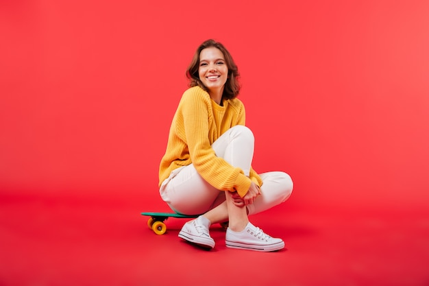 Retrato de uma menina feliz, sentado em um skate