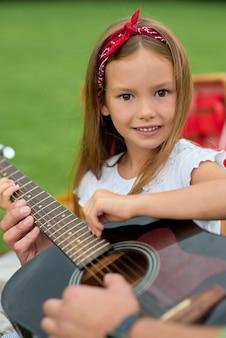 Retrato de uma menina feliz sorrindo para a câmera enquanto está sentado com o pai na grama verde do parque