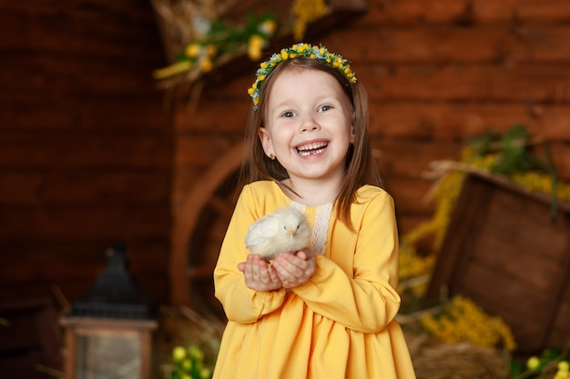 Retrato de uma menina feliz, uma criança tem uma galinha nas mãos