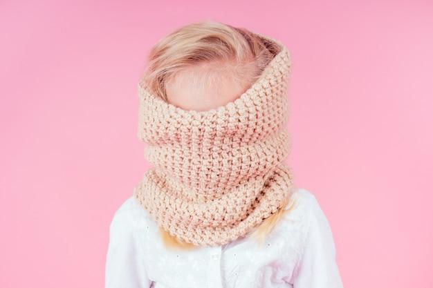 Retrato de uma menina feliz vestindo blusa e cachecol de malha. criança brincando de esconde-esconde no fundo rosa no estúdio. conceito de venda da moda outono inverno.