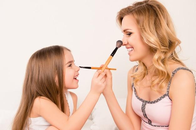 Retrato de uma menina fofa e sua mãe fazendo maquilagem uma à outra