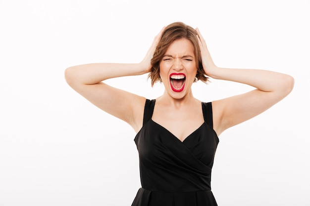 Retrato de uma menina frustrada, vestida de vestido preto, gritando