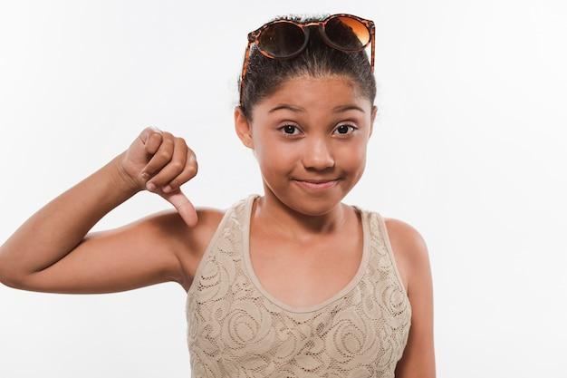 Retrato de uma menina gesticulando polegares para baixo sobre fundo branco