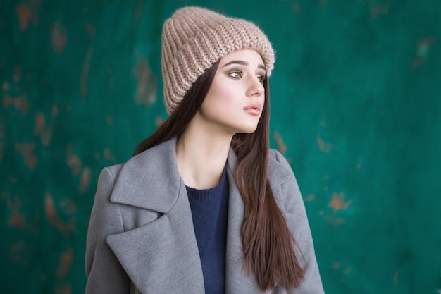 Retrato de uma menina hippie com cabelos castanhos compridos, vestindo um casaco elegante e boné de malha está olhando para o lado em pé sobre um fundo de cerca de arte verde escuro em um estúdio. mock up horizontal.