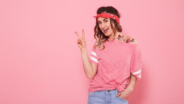 Retrato de uma menina hippie com tatuagem, isolada na parede rosa