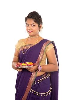 Retrato de uma menina indiana tradicional segurando pooja thali com diya, diwali ou deepavali