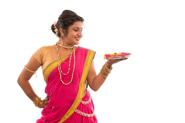Retrato de uma menina indiana tradicional segurando pooja thali com diya durante o festival de luz em branco