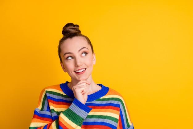 Retrato de uma menina inspirada positiva tocando a mão queixo olhar copyspace pensar pensamentos usar um suéter isolado sobre um fundo de cor brilhante