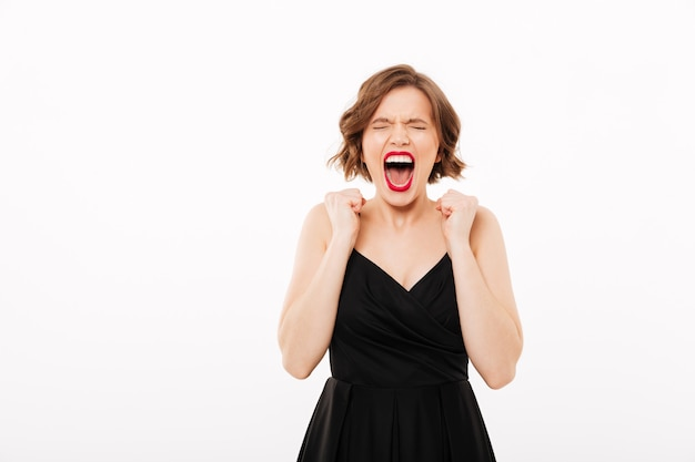 Retrato de uma menina irritada, vestida de vestido preto, gritando