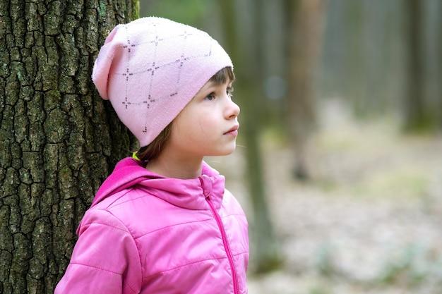 Retrato de uma menina jovem bonita vestindo uma jaqueta rosa e boné inclinado para uma árvore na floresta