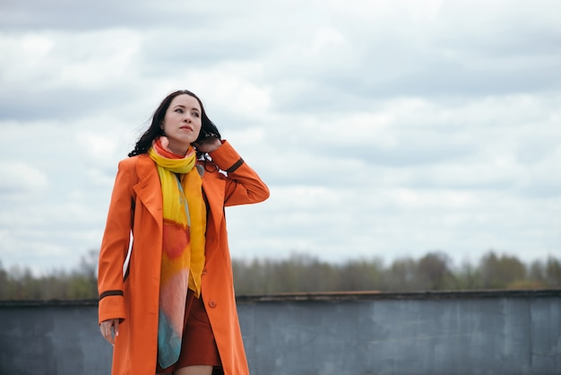 Retrato de uma menina linda com cabelos cacheados pretos na capa laranja e lenço brilhante lanxess
